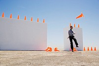 Businessman kicking traffic cones outdoors with two walls