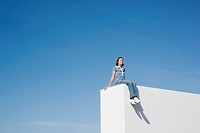 Woman sitting on wall outdoors with blue sky