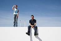 Man and woman on wall outdoors with ladder