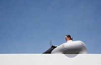 Businesswoman on beanbag chair with laptop outdoors