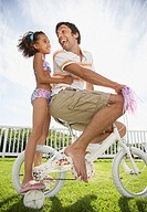 Father and daughter on bicycle with streamers smiling