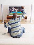 A man excitedly watching the television