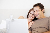 A couple reclining in bed using a laptop