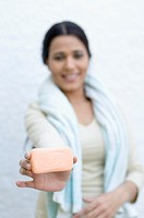 Portrait of a young woman holding a bar of soap