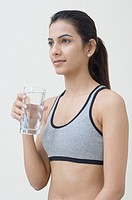 Side profile of a young woman holding a glass of water