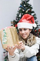 Young woman holding a gift and smiling