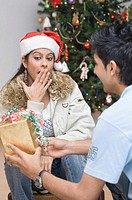 Rear view of a young man giving a Christmas present to a young woman