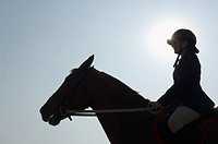 Silhouette of a female jockey riding a horse