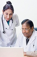 Male doctor using a laptop with a female doctor standing beside him