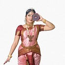 Young woman performing Bharatnatyam and holding a CD