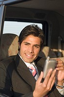 Close-up of a businessman using a personal data assistant in a car