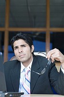 Businessman in front of a laptop and thinking