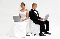 Bride and groom on laptops