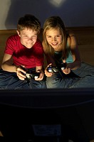 Boy and girl playing on a game console