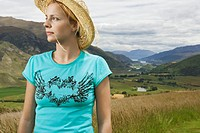 Woman wearing cowboy hat in countryside