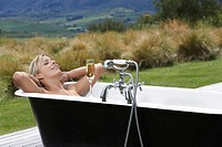 Woman taking bath with champagne on porch in countryside (thumbnail)