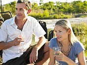 Portrait of man and woman holding wineglasses outdoors