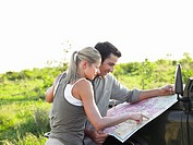 Man and woman looking at map on bonnet of jeep
