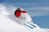 man skiing on slope sending up snow spray