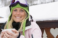 Young woman in ski-wear, holding cup Close-up, high angle, portrait