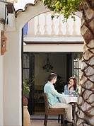 Couple sitting on garden terrace having drinks