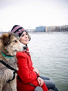 Young woman sitting by river with dog focus on woman