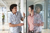 Two office workers talking at glass door in office