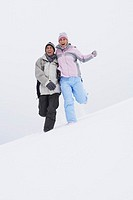 Couple running down snow_covered hill low angle view