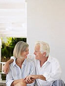 Senior couple sitting on verandah looking in eyes and smiling (thumbnail)