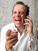 Businessman on the phone pointing at camera and laughing ,
