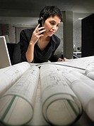 Female architect using mobile phone, looking at plans on desk