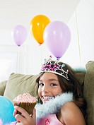 Young girl 7_9 sitting on sofa eating cupcake close_up