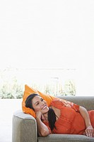 Mid_adult woman lying on sofa smiling