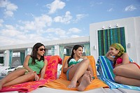 Three teenage girls 16_17 lying on sunloungers