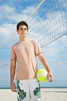 Teenage boy 16_17 standing on beach volleyball court portrait