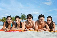 Group of teenagers 16_17 lying in row on beach towels portrait