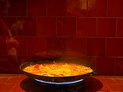 Steaming dish of paella cooking on gas stove