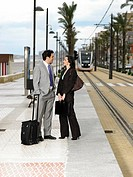 Businessman and businesswoman talking on pavement by tram tracks