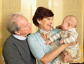 Senior grandparents with baby grandson 1-3 months smiling