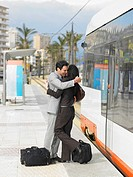 Businessman and businesswoman embracing by tram