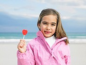 Young girl 6-8 holding lollipop in front of sea, close-up, portrait Alicante, Spain