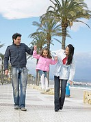 Mother and father walking along palm lined pavement by the sea swinging young daughter 6-8 Alicante, Spain