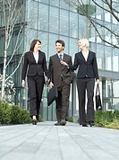 Three business people walking outside office building talking and smiling surface view