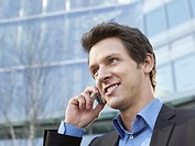 Mid adult businessman in front of office building using mobile phone