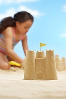 Girl 7_9 years building sand castles on beach focus on sand castle in foreground