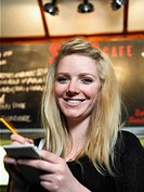 Young waitress holding notepad in cafe, smiling, portrait