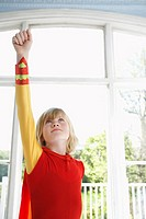 Portrait of young boy 7_9 in superhero costume with raised fist looking up