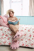 Young girl 5_6 sitting on bed wearing bunny costume and monster slippers reading book