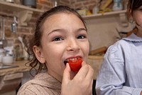 Girl 5-7 eating tomato, close-up, portrait