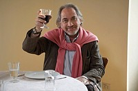 Senior man holding up wine at table, portrait
